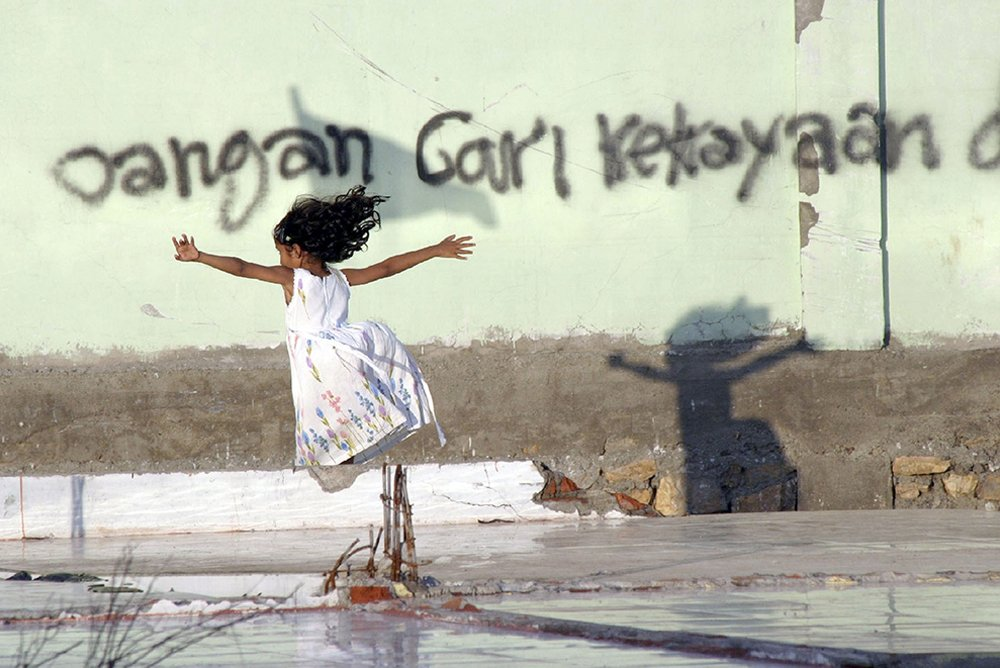 Girl plays with her shadow near the remains of her home in tsunami-ravaged Banda Aceh, Indonesia, 2004.